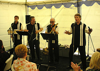 Here's our hard-working, ultrafunky '50's-'60's oldies group, Daddy Cool, sweatin' it out in a live performance in 2008. Personnel (L to R): Bill New (bass vocal and bongos), Randy Crenshaw (baritone vocal), Craig Copeland (tenor vocal and electric guitar), and Danny Faragher (lead vocal and harmonica).