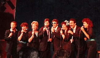 One of the various a cappella vocal groups I've been a member of in L.A., Eight To The Bar. This would have been shortly after my stint in the L.A. Jazz Choir, and several of these singers besides myself were indeed veterans of LAJC. This is us on stage at an At My Place gig in Santa Monica, circa 1985. Personnel, L to R: Stewart Wilson-Turner, Jan Roper, Barbara Bentree, Randy Crenshaw, Bill New, Pam Austin, Gary Rosen, Robin Ehlers. Note the extreme mic-holding hand precision!
